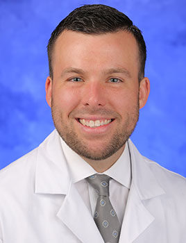 Photo of Christopher Weller, MD, pictured wearing white medical coat