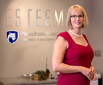 Dr. Jessyka Lighthall is standing in front of a desk. Pictured behind her is Esteem Penn State Health Cosmetic Associates signage on the wall.