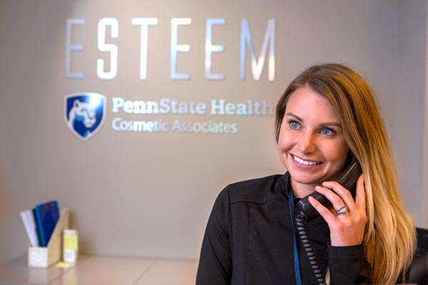 """An """"Esteem"""" staff member is answering the phone from the """"Esteem"""" reception desk."""